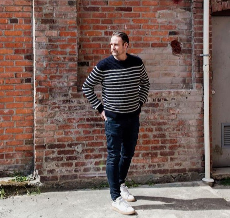 man wearing merino wool ribbed stripe navy and cream colour sweater and jeans