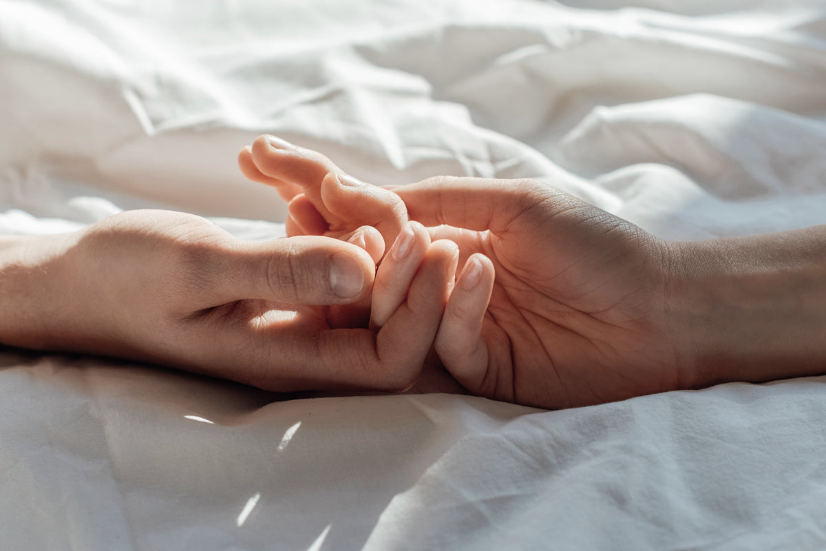 Closeup of couple holding hands on a sheet