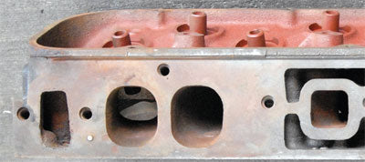 """Stock iron oval ports from a """"206"""" casting head. Note distance from the ports to the center bolt-hole above the pair of runners"""