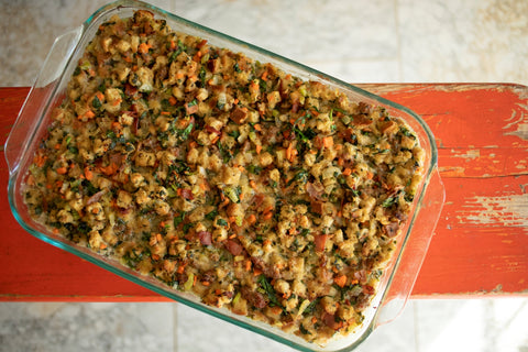 Oyster Stuffing in a clear pan on a red bench