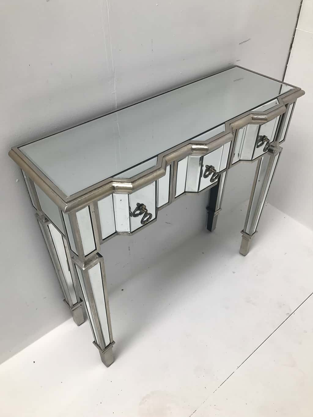Charleston mirrored console table with 3 drawers, silver wood edging, glass top, tapered legs and drop Ring brass pulls