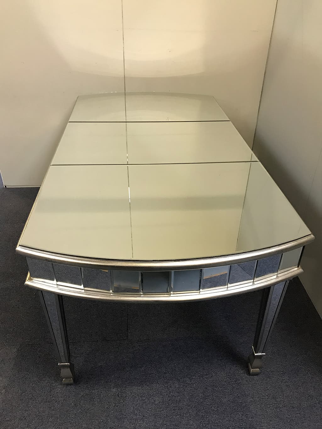 6 seater mirrored dining table with bowed ends, bordered with 9cm bevelled mirror strips, edged with wood finished in an antiqued silver finish, wood and mirror