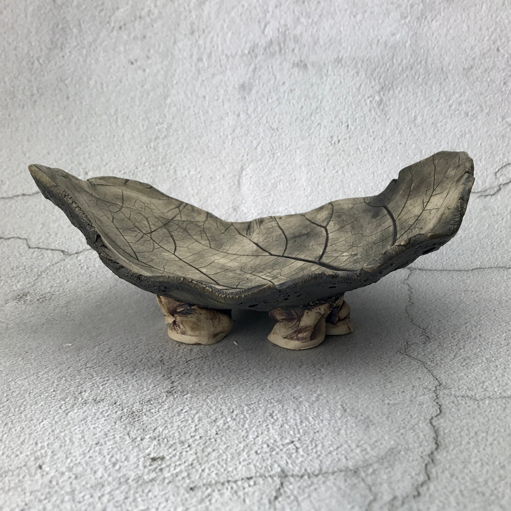 Black leaf impression on irregular shaped bowl with freeform feet.
