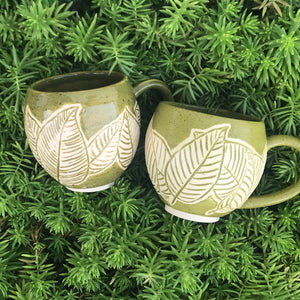 Green mug with carved leaf patterns on green grass background
