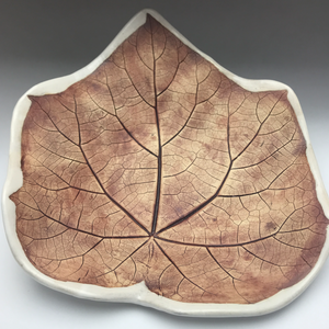 ceramic plate with iron brown leaf imprint and white edges