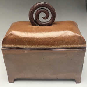 rich brown rectangular box with curved lid and dark brown handle with spiral pattern