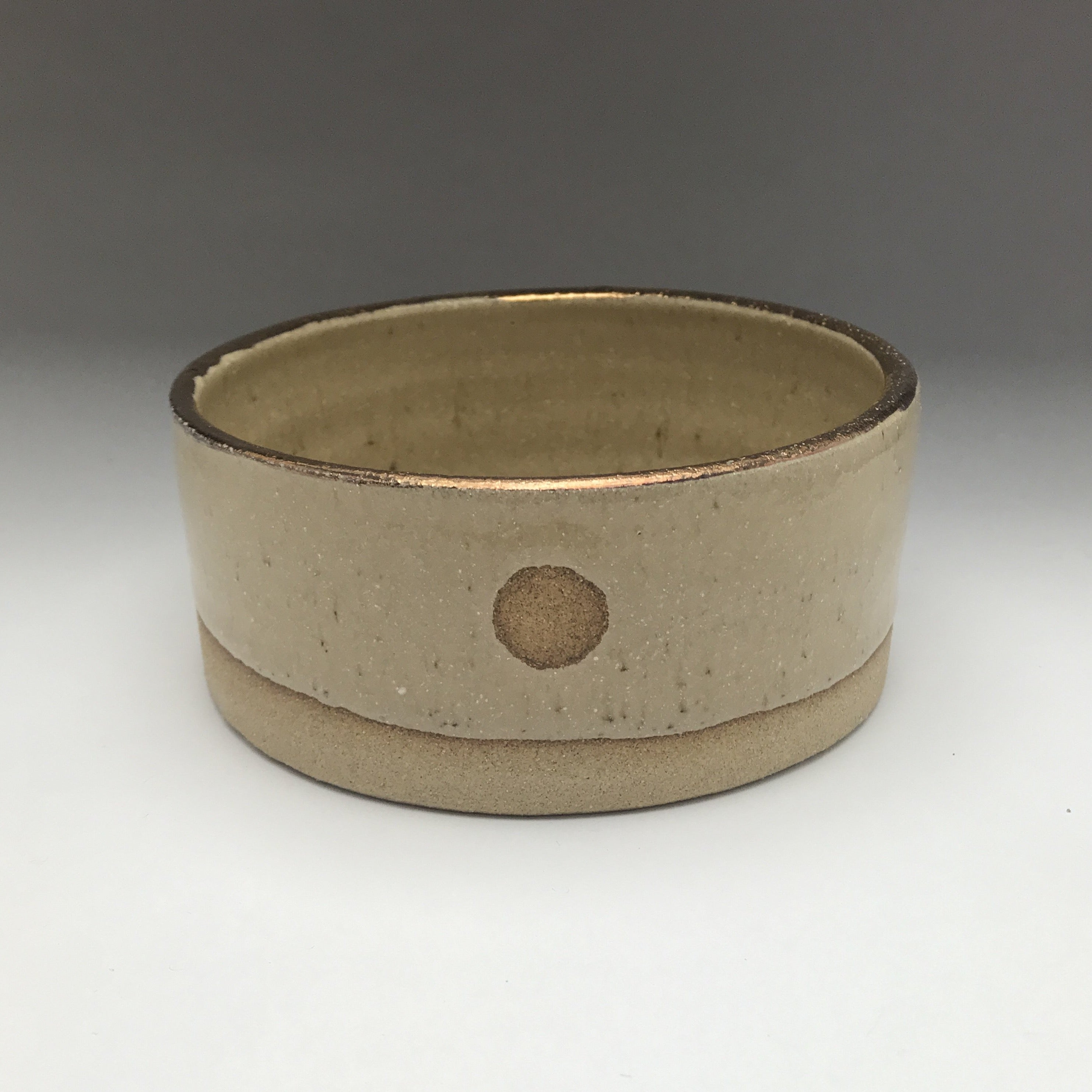 cylinder shaped ceramic dish with bare clay, creamy beige glaze, circle accent detail and real gold accent on the rim.