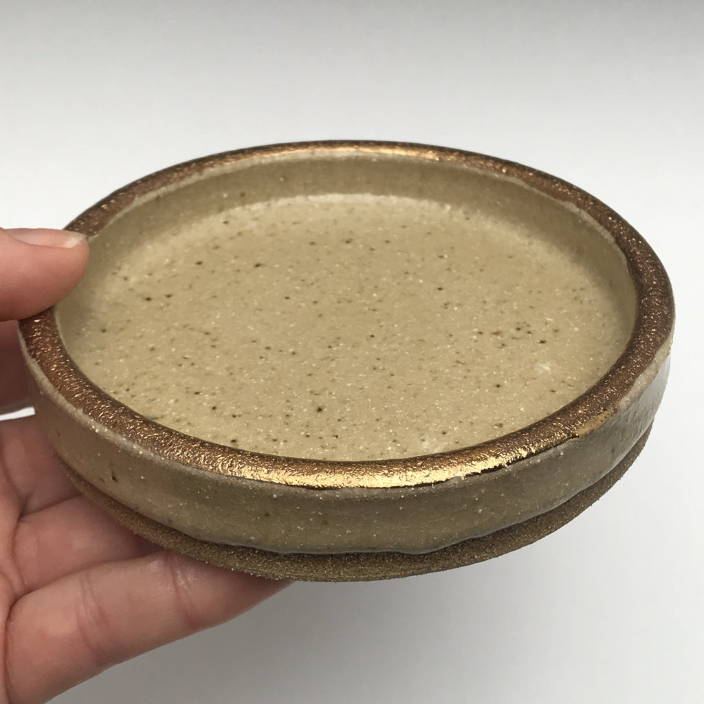 cylinder shaped ceramic dish with bare clay, creamy beige glaze and real gold accent on the rim.