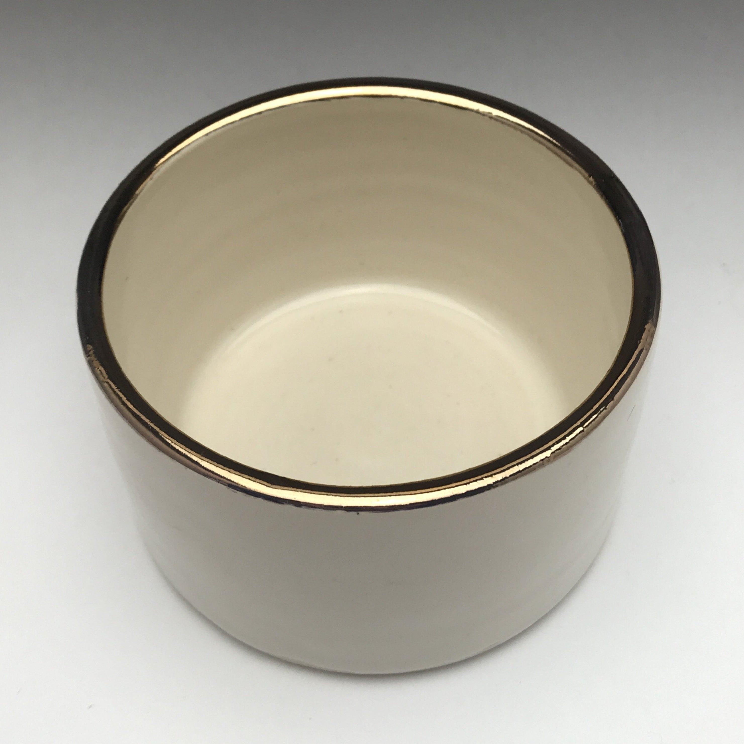 cylinder shaped ceramic dish with creamy white glaze and real gold accent on rim