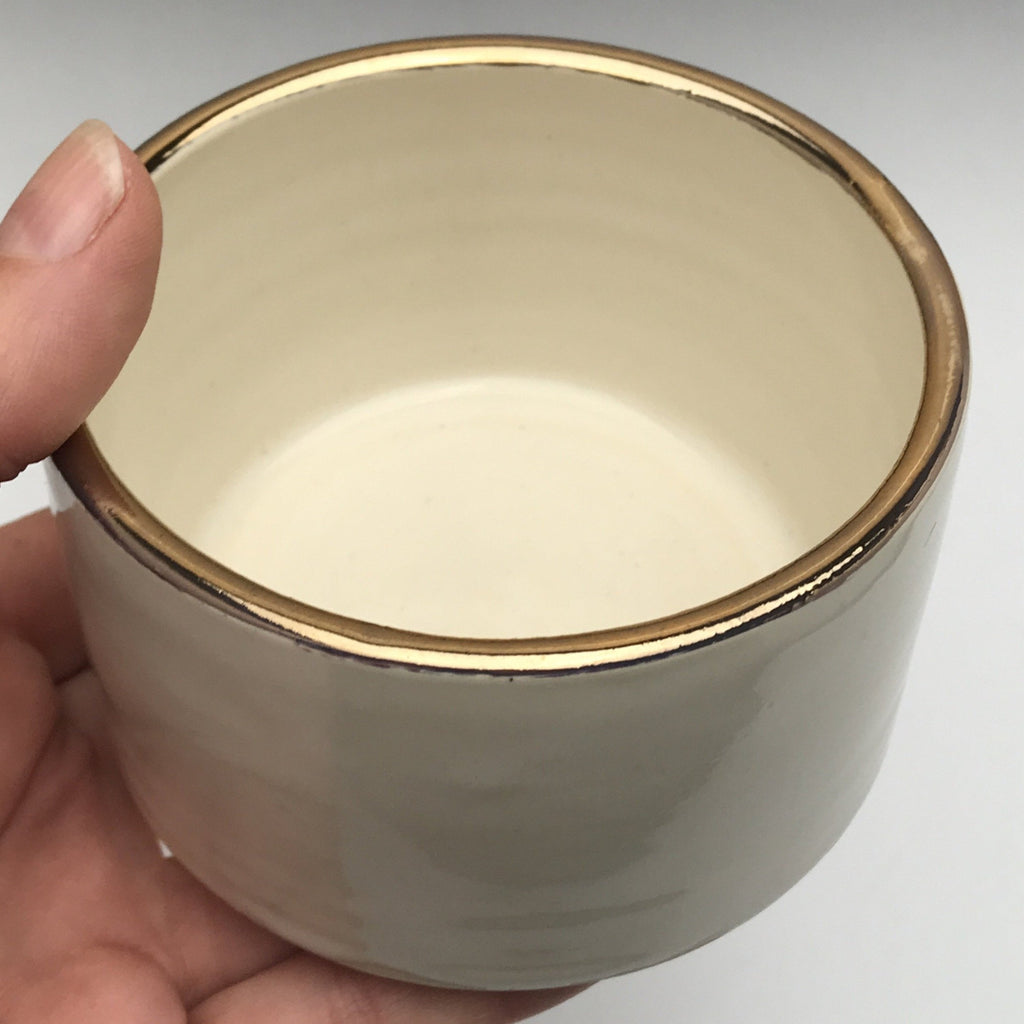 cylinder shaped ceramic dish with creamy white glaze and real gold accent on the rim.