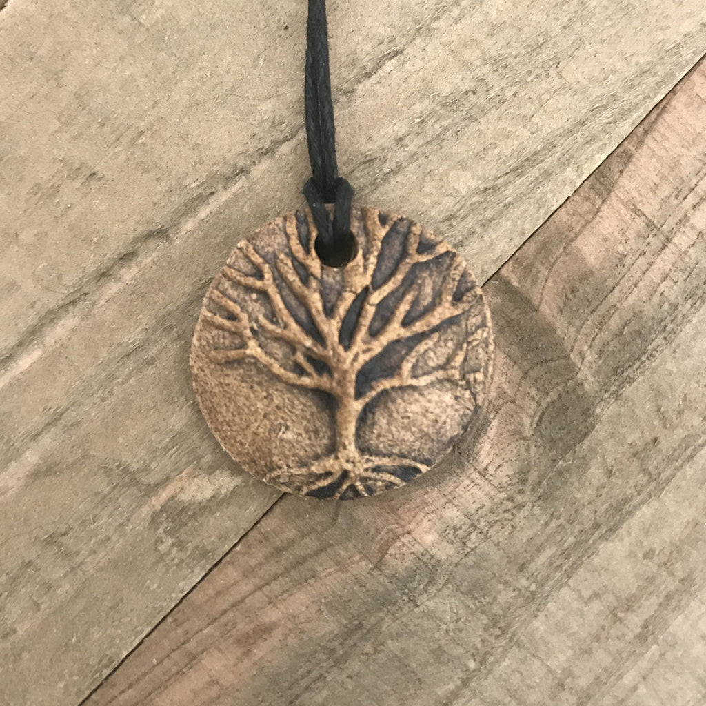 Round pendant necklace with tree of life. Made of clay, brown color.