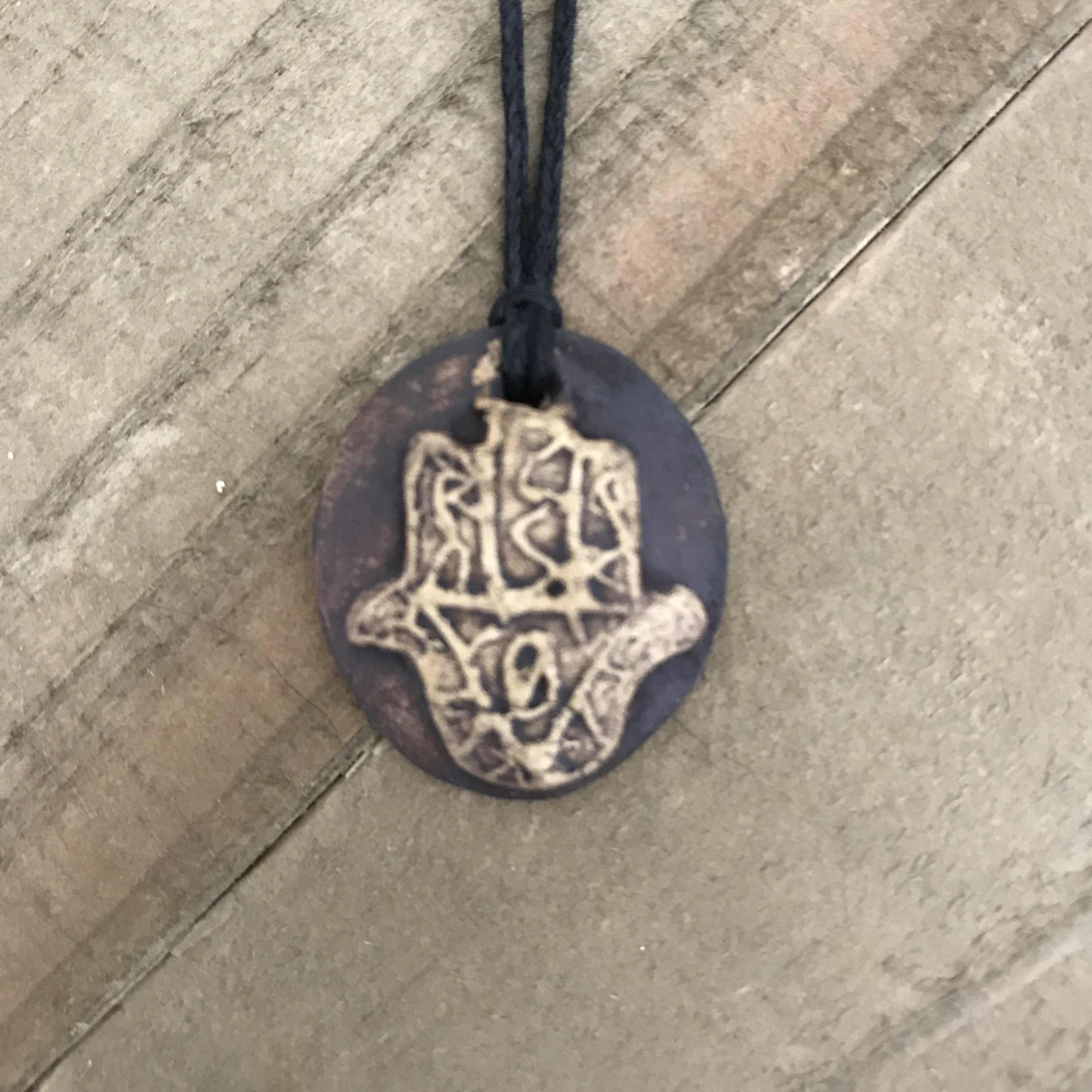 Oval pendant necklace with Hand of God or Hamsa. Made of clay, brown color.