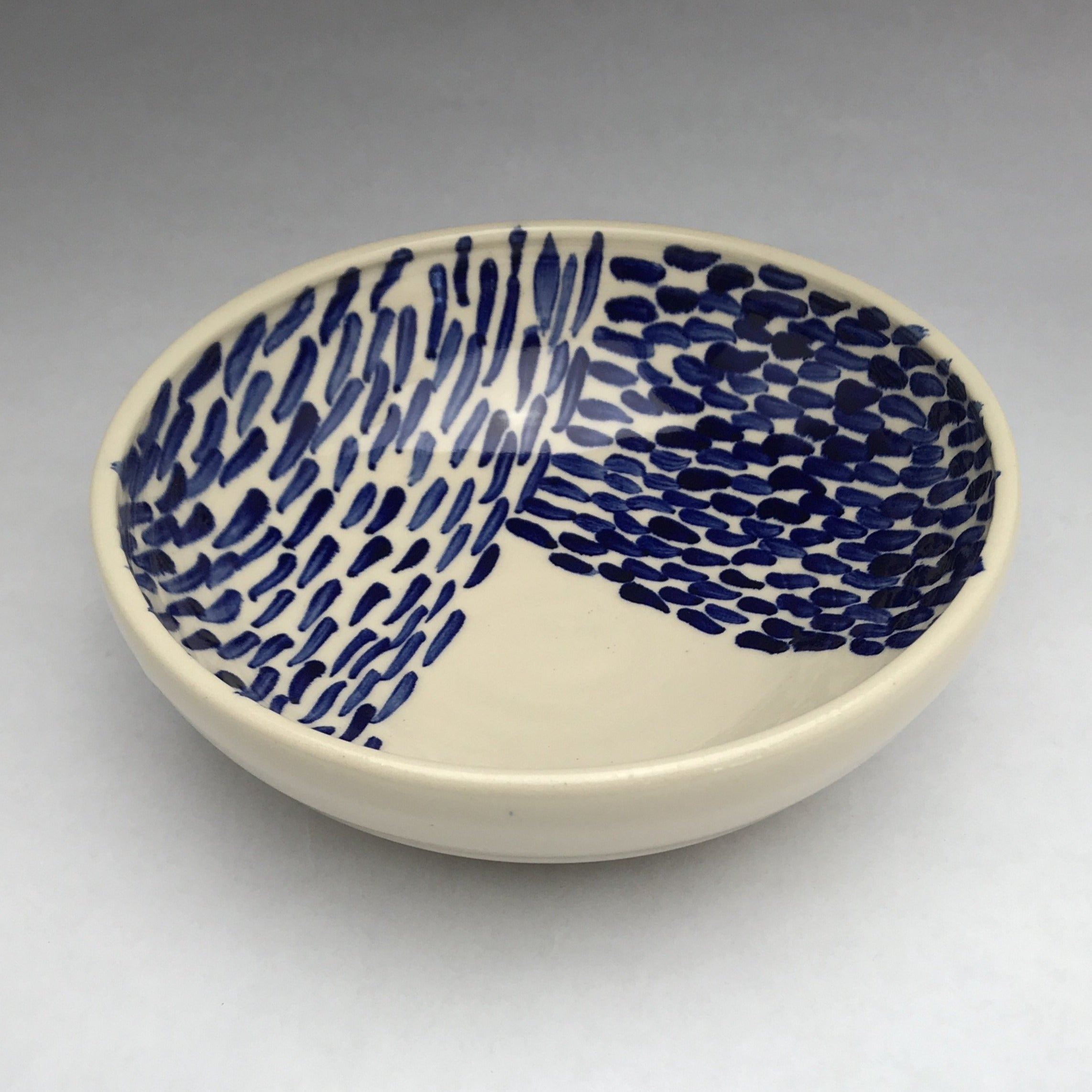 white ceramic bowl with cobalt blue patterns of lines and dots