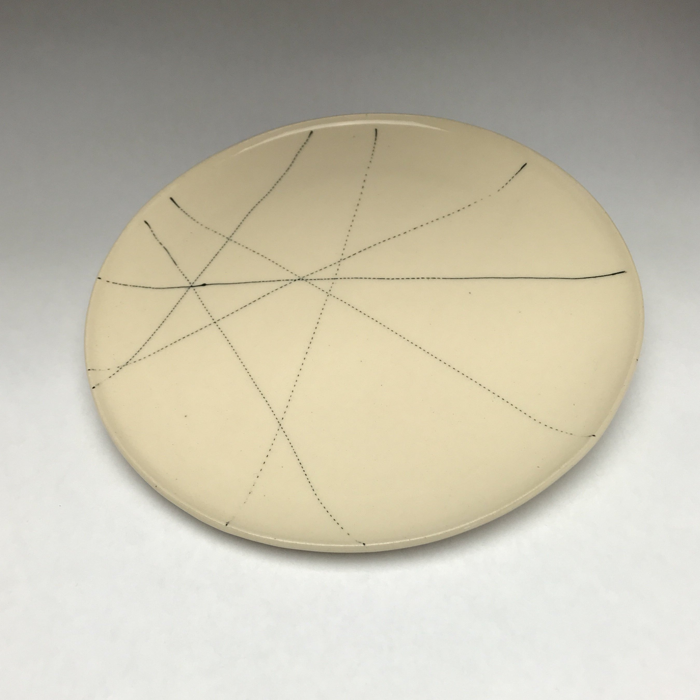 white ceramic plate with black graphic linework reminiscent of graffiti
