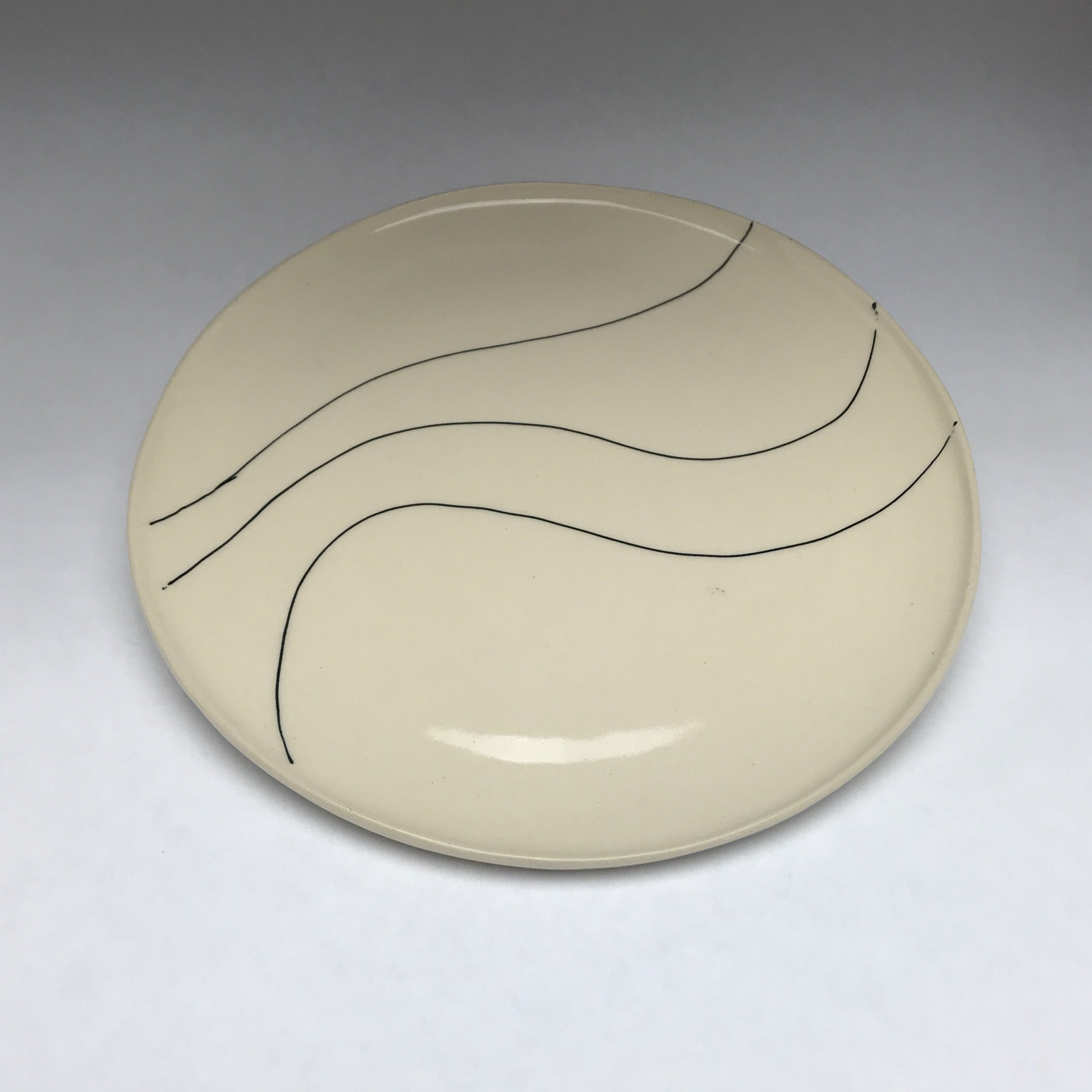 ceramic plate with black graphic linework reminiscent of graffiti