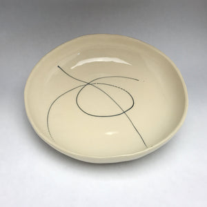 white ceramic bowl with black graphic linework reminiscent of graffiti