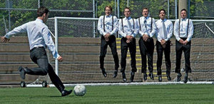 Groom kicking soccer ball at Groomsman
