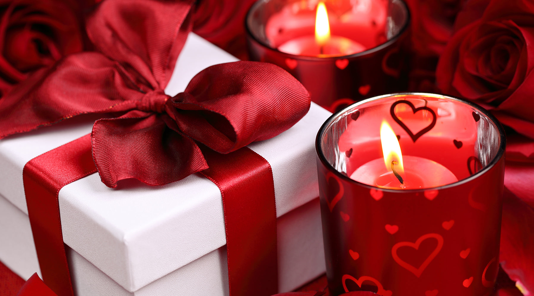 a white giftbox alongside with a candle in a red container with roses in back