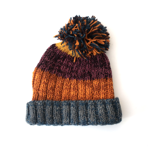 unisex striped bobble hat in purples and oranges