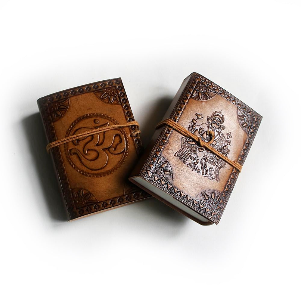 two pocket-sized leather journals featuring Om symbol and Ganesha embossed detail