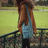 model wearing turquoise diamond shoulder bag