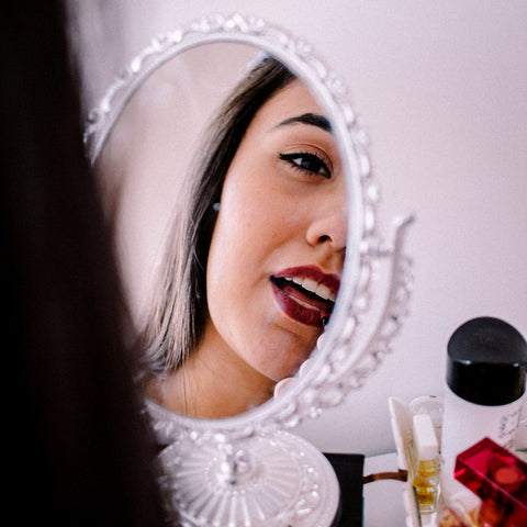 reflection of woman in mirror putting on dark red lipstick