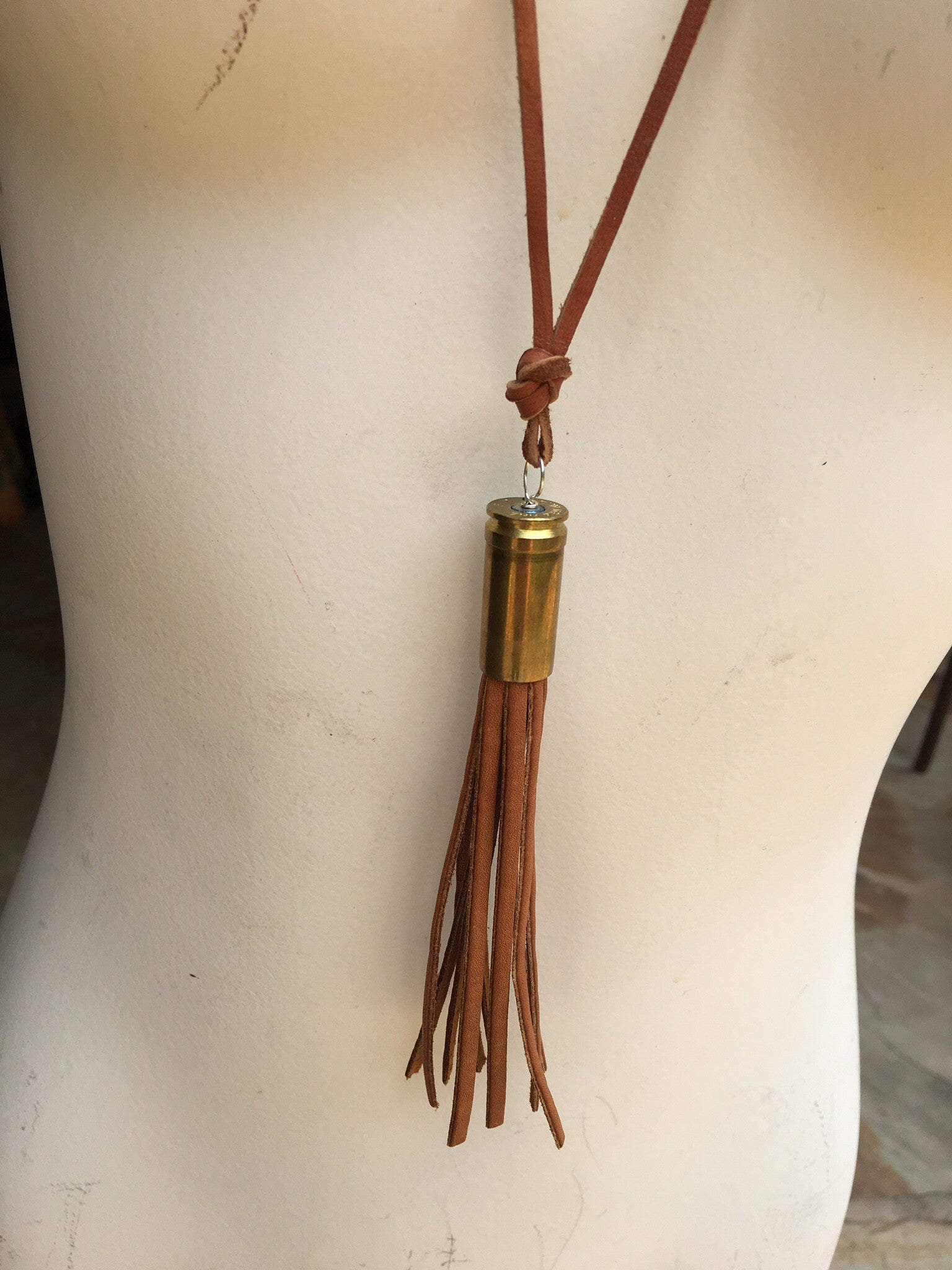 Jewelry, bullet with leather fringe on leather rope.