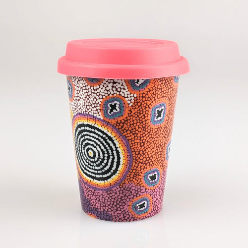 Coffee cup with hot pink, orange white and blue indigenous design printed on it.