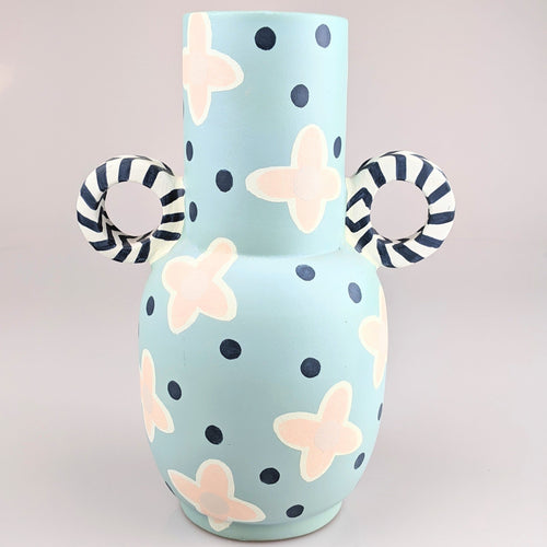 Blue tall vase with navy handles and dots, with pink flowers scattered around vase.
