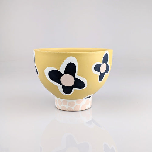 Yellow bowl with dark navy, pink flowers painted on it.