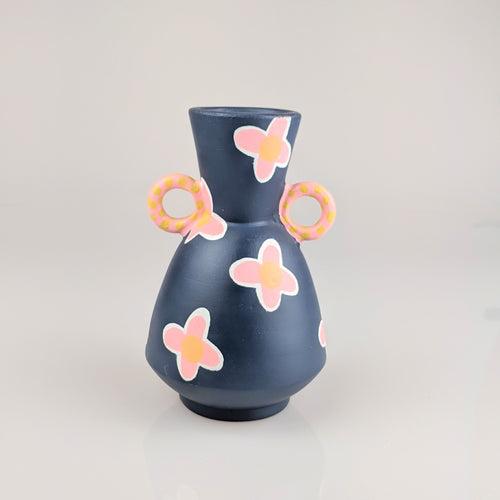 Small navy blue vase with peach flowers painted on it.