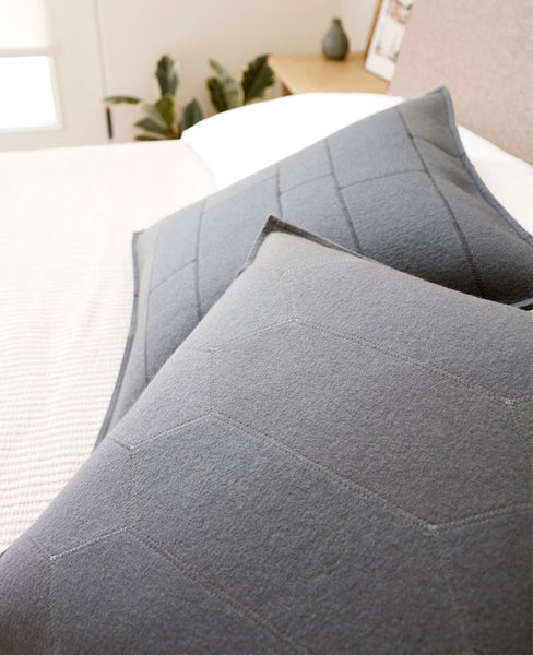 Grey wool felt throw pillows on a bed