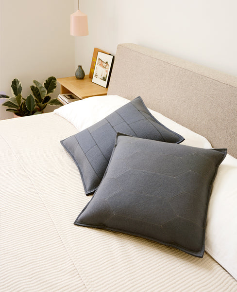 Grey wool felt throw pillows on a modern bed