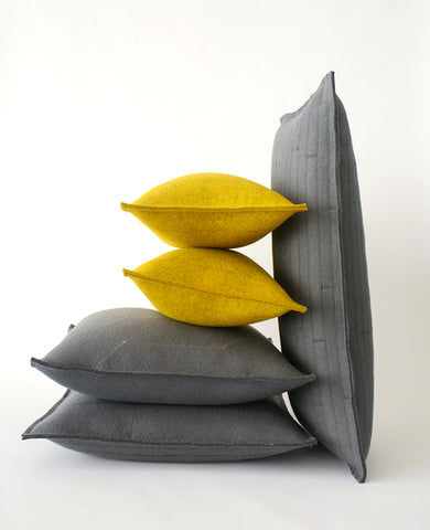 Pile of gold and grey wool felt throw pillows