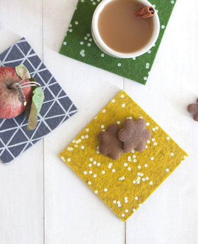 Colorful patterned felt coasters with fall snacks and apple cider