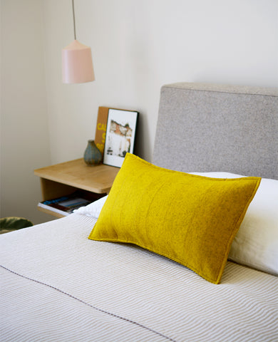 Gold wool felt lumbar pillow in a bedroom