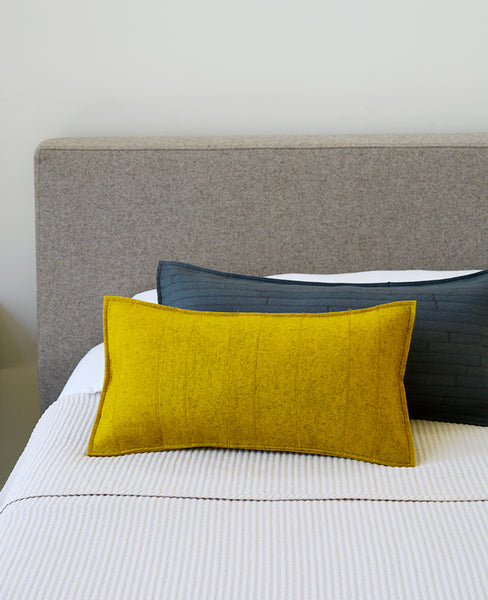 Gold wool felt lumbar pillows on a modern bed