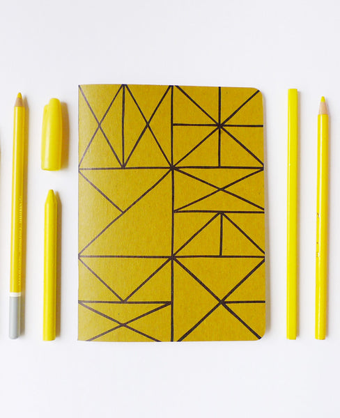 Grid notebook with yellow pencils