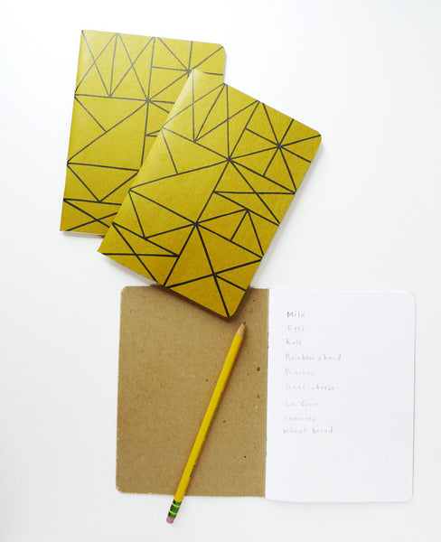 Three gold grid notebooks - one open with a pencil