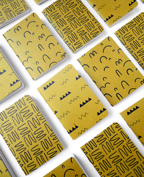 Gold ochre patterned notebooks tiled on a table