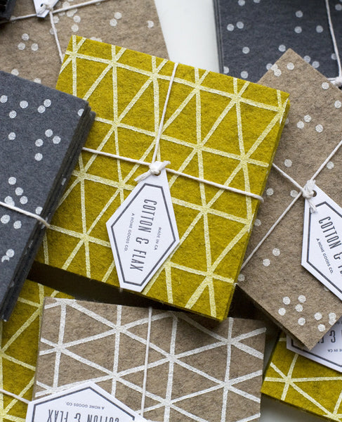A pile of patterned coaster sets in gold, grey, and beige