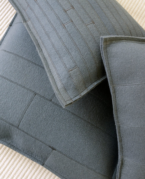 Pile of grey wool felt throw pillows