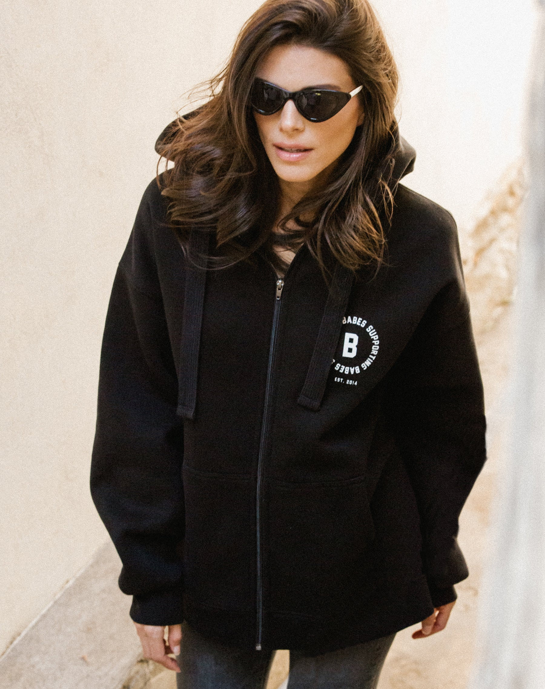 Photo of the Babes Supporting Babes big sister zip up hoodie in black by Brunette the Label.