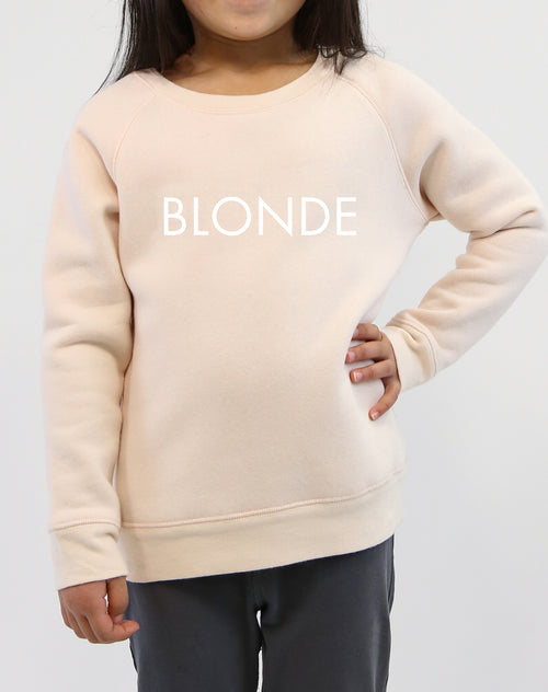 Photo of child wearing the Blonde classic crew neck sweatshirt in peach crush by Brunette the Label.