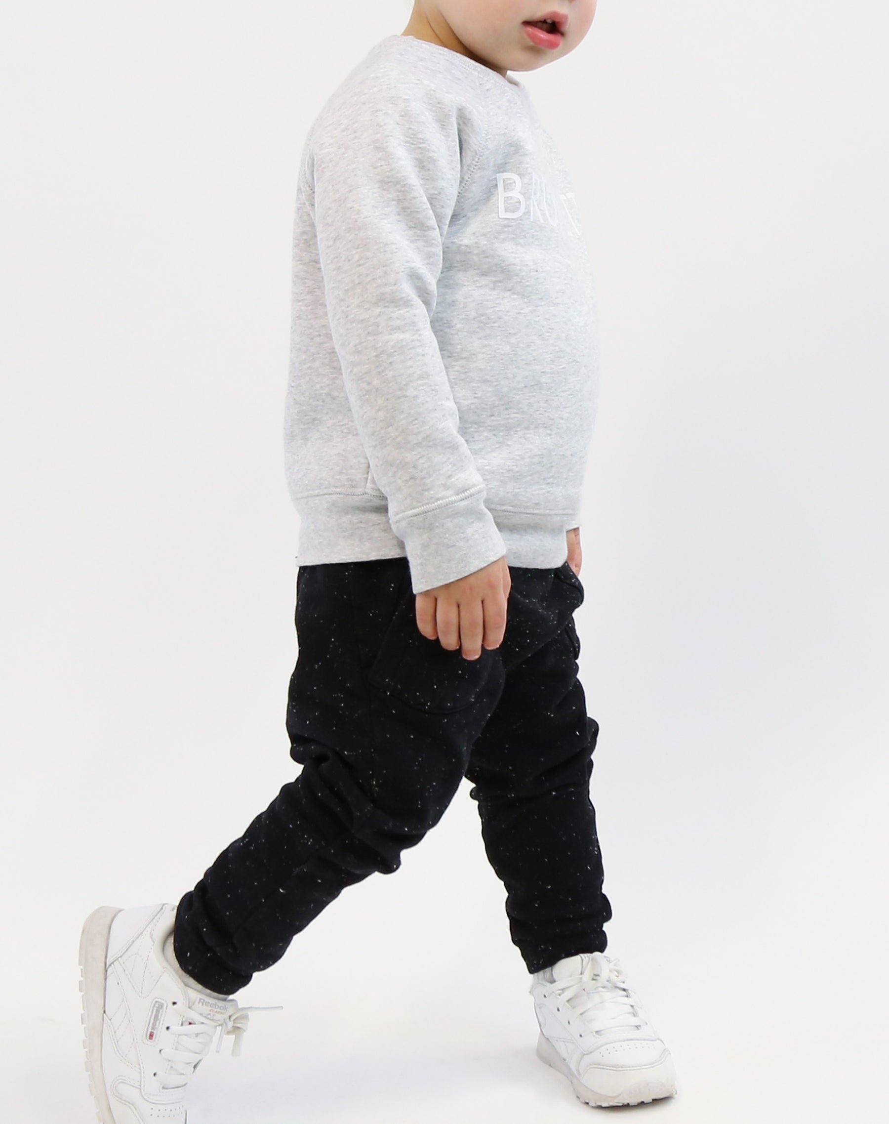 Photo of child walking in the Brunette classic crew neck sweatshirt in pebble grey by Brunette the Label.