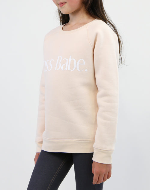Side photo of child wearing the Boss Babe classic crew neck sweatshirt in peach crush by Brunette the Label.