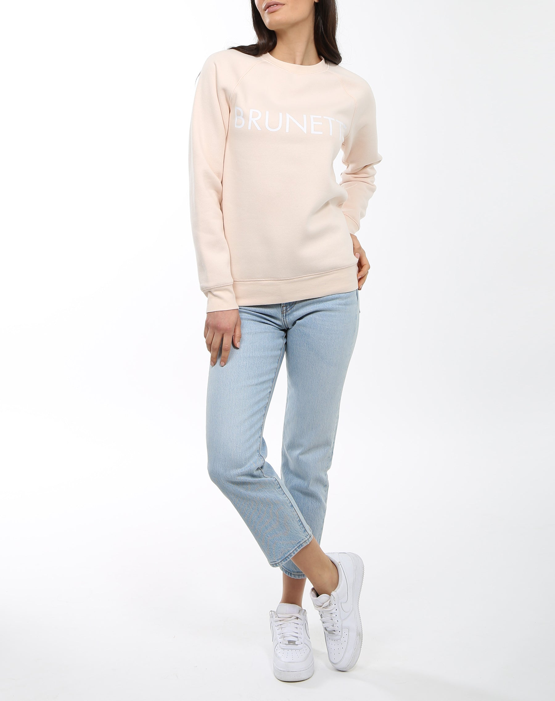 A full body photoraph of a model wearing the Brunette Crew Neck Sweatshirt in Peach Crush by Brunette the Label.