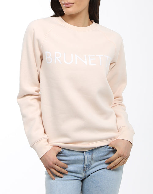 A model is photographed wearing the Brunette Crew Neck Sweatshirt in Peach Crush by Brunette the Label.