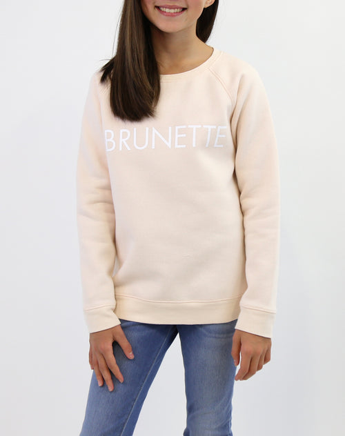Photo of child wearing the Brunette classic crew neck sweatshirt in peach crush by Brunette the Label.