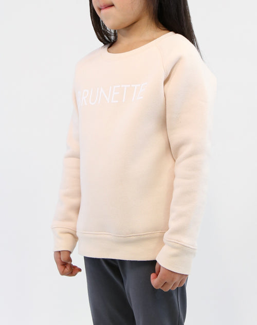 Side photo of child wearing the Brunette classic crew neck sweatshirt in peach crush by Brunette the Label.